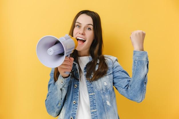 Kobieta krzycząca w megafonie robi gest zwycięzcy