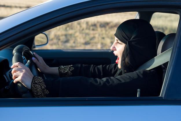 Kobieta krzyczy śpiewając piosenki podczas jazdy samochodem.,