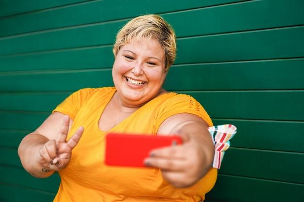 Kobieta krzywego robienia selfie z telefonu komórkowego na zewnątrz