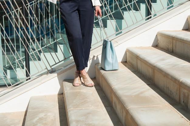Kobieta krzyżowała nogi w czarnych spodniach stojących na schodach
