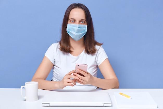 Kobieta księgowa pracująca w domu, ubrana w maskę ochronną, pani moderator podczas kwarantanny dla koronawirusa wykonująca swoją pracę zdalnie