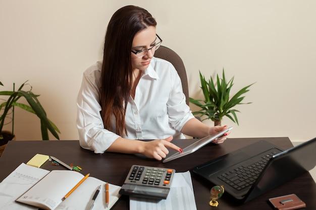 Kobieta księgowa trzymając się za ręce komputera typu tablet