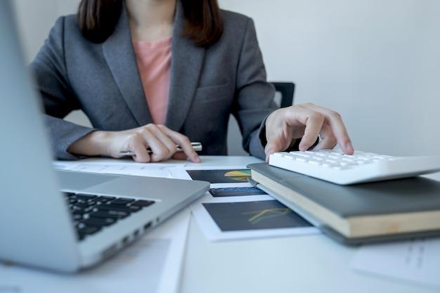 Kobieta księgowa używa kalkulatora i analizuje wykres z laptopem w biurze domowym