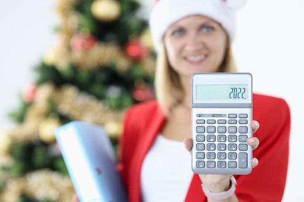 Kobieta księgowa w kapeluszu świętego mikołaja posiada kalkulator na tle choinki. podsumowanie koncepcji raportu rocznego