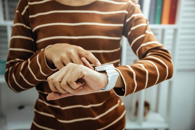 Kobieta księgowego patrząc czas pod ręką zegarki w nowoczesnym biurze marzy o weekendowych wakacjach z widokiem z okna.