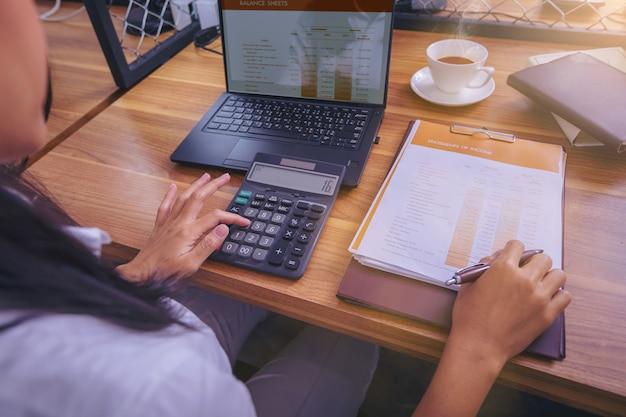 Kobieta księgowy pracuje używać kalkulatora dla kalkuluje pieniężnego raport przy miejscem pracy.