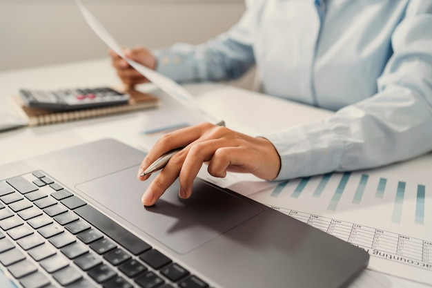 Kobieta księgowy używać kalkulatora i komputera z przytrzymaniem pióra na biurku w biurze. koncepcja finansowo-księgowa