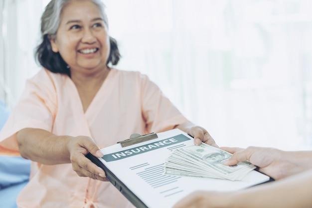 Kobieta, która doznała uszczerbku na zdrowiu osób starszych na łóżku pacjenta w szpitalu, trzymając nas banknotów dolarowych, czuje się szczęśliwa z otrzymywania pieniędzy ubezpieczeniowych od firm ubezpieczeniowych