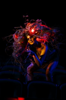 Kobieta, która gra w teatrze rolę ducha lub ducha, siedzi między rzędami krzeseł