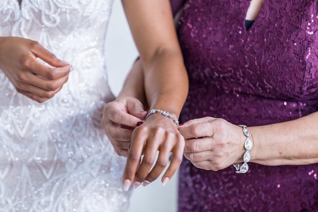 Kobieta, która pomaga założyć bransoletkę na nadgarstek panny młodej