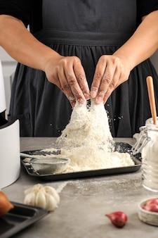 Kobieta, która robi domowe chrupiące smażonego kurczaka, panieruje kurczakowe podudzia z mąką w kuchni
