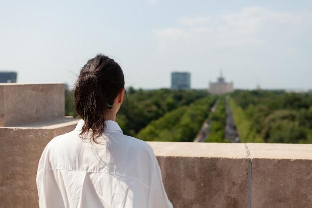 Kobieta, która stoi na dachu budynku i cieszy się panoramicznym widokiem
