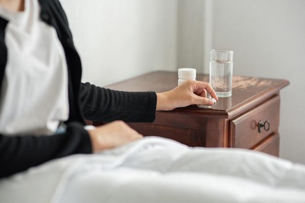 Kobieta, która źle się czuje na kanapie i ma zamiar zażyć antybiotyki.