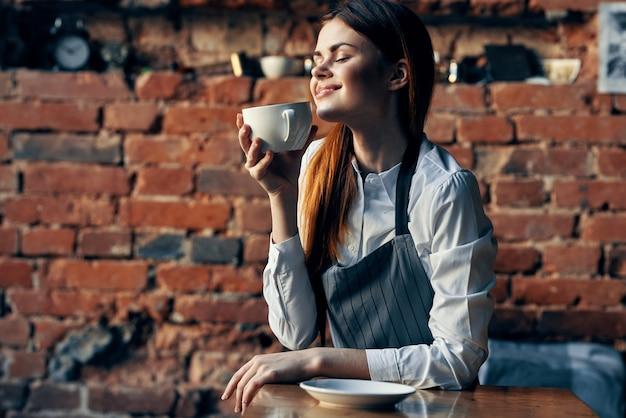 Kobieta kubek kawy kelner siedzi przy stole zabawy pracy