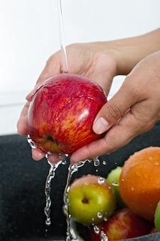 Kobieta kucharka myje jabłko pod bieżącą wodą z kranu
