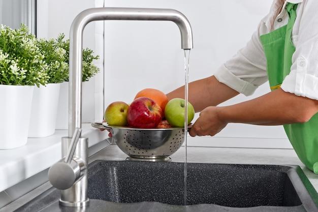 Kobieta kucharka myje owoce pod bieżącą wodą z kranu.