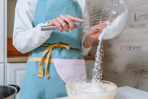 Kobieta-kucharz dodaje mąkę do ciasta. proces mieszania składników ciasta w domowej kuchni