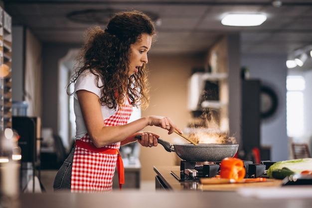 Kobieta kucharz gotowania warzyw na patelni