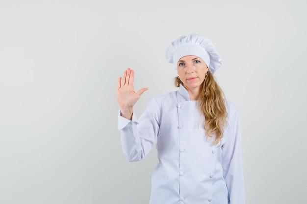 Kobieta kucharz macha ręką, by się pożegnać w białym mundurze i wygląda cicho
