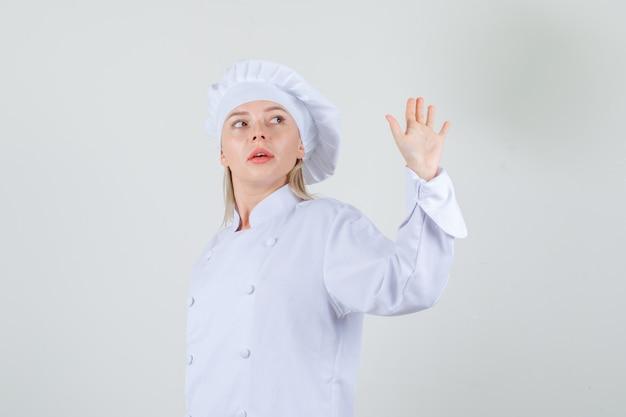Kobieta kucharz macha ręką, patrząc wstecz w białym mundurze.