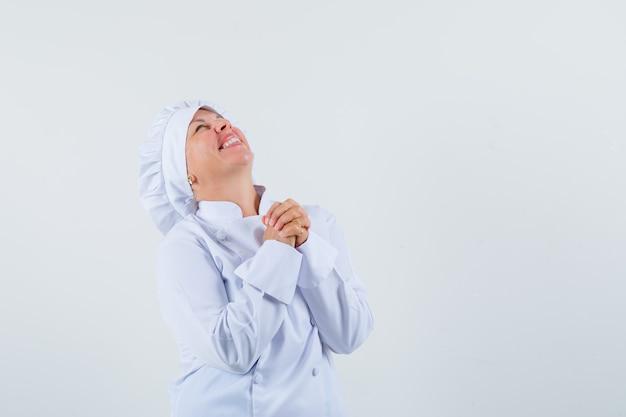 Kobieta kucharz marzy o czymś w białym mundurze i wygląda entuzjastycznie. miejsce na tekst