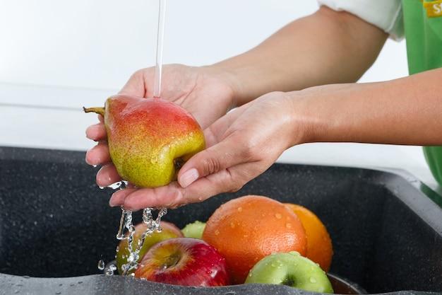 Kobieta kucharz myje gruszkę pod wodą wypływającą z kranu.
