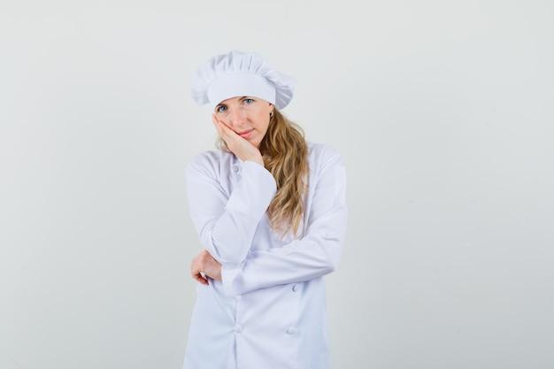 Kobieta kucharz opierając policzek na uniesionej dłoni w białym mundurze i wyglądająca rozsądnie