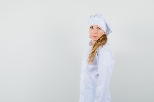 Kobieta kucharz patrząc na kamery w białym mundurze i wyglądający rozsądnie. .