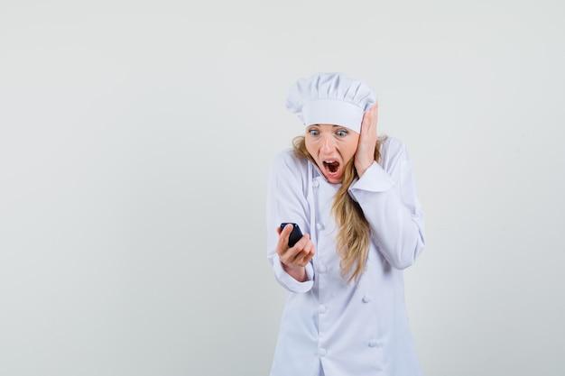 Kobieta kucharz patrząc na telefon w białym mundurze i patrząc zszokowany.