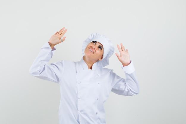 Kobieta kucharz patrząc w górę, podnosząc dłonie w białym mundurze i wyglądając wesoło.
