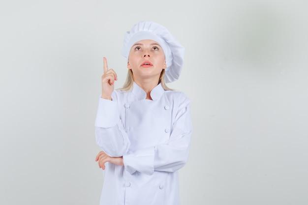 Kobieta kucharz patrząc z palcem w białym mundurze