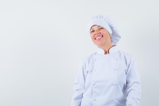 Kobieta kucharz patrząc z przodu w białym mundurze i patrząc wesoło
