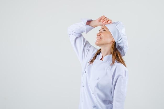 Kobieta kucharz patrząc z ręką na głowie w białym mundurze i patrząc zadowolony. .