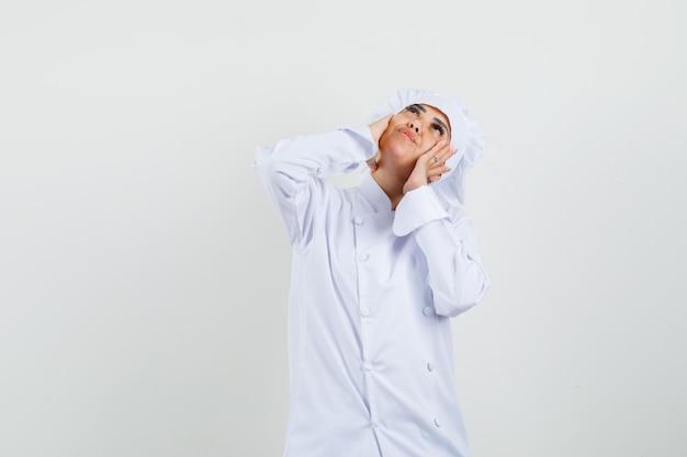 Kobieta kucharz patrząc z rękami na policzkach w białym mundurze i wyglądający marzycielsko