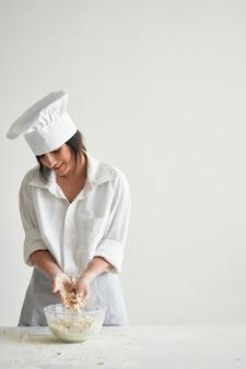 Kobieta kucharz piekarz rozwija ciasta pracy gotowania mąki. zdjęcie wysokiej jakości