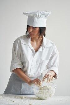 Kobieta kucharz piekarz rozwija ciasto do gotowania mąki