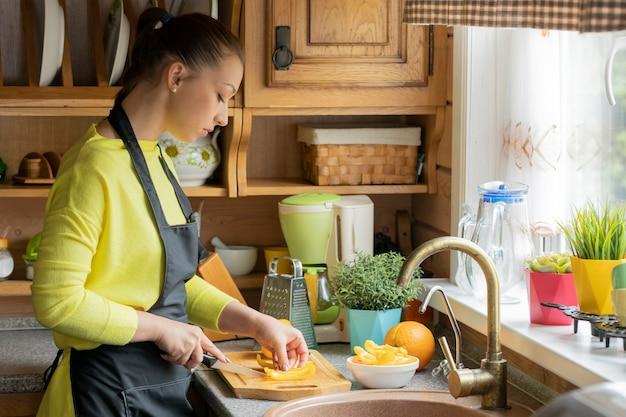 Kobieta kucharz plasterki słodkiej papryki na desce