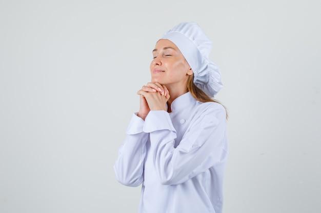 Kobieta kucharz podpiera brodę na splecionych dłoniach w białym mundurze i wygląda z nadzieją.