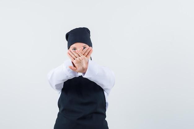 Kobieta kucharz pokazuje gest stop w mundurze, fartuchu i wygląda poważnie, widok z przodu.