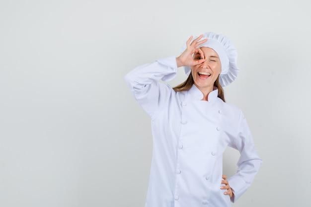 Kobieta kucharz pokazuje ok gest na oko w białym mundurze i wygląda optymistycznie. przedni widok.