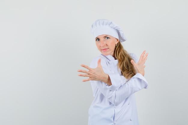 Kobieta kucharz pokazuje palce ze skrzyżowanymi rękami w białym mundurze i wygląda pewnie.