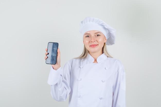 Kobieta kucharz pokazuje smartfon i uśmiecha się w białym mundurze i wygląda wesoło.