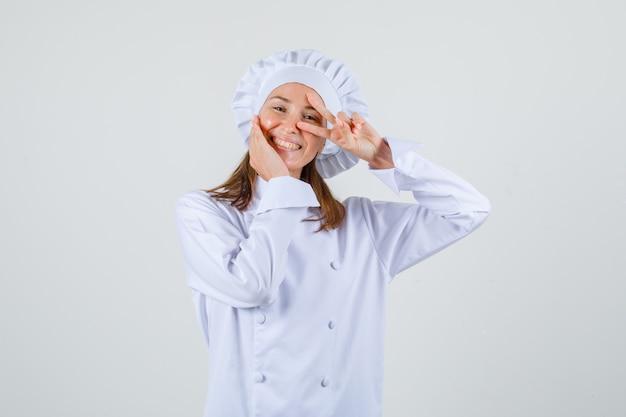 Kobieta kucharz pokazuje znak v blisko oka w białym mundurze i wygląda wesoło. przedni widok.