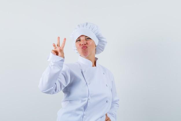 Kobieta kucharz pokazuje znak v w białym mundurze i wygląda pewnie