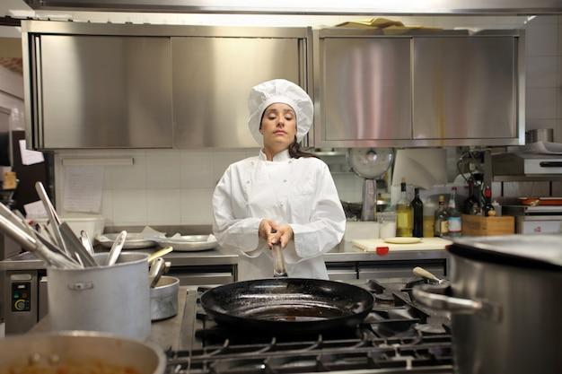 Kobieta kucharz pracuje w kuchni