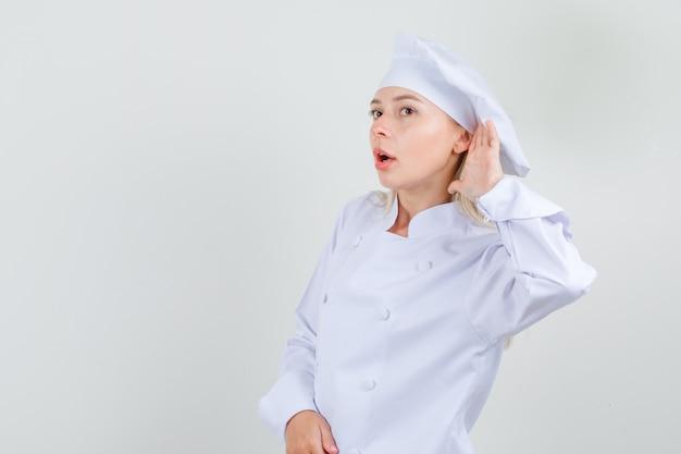 Kobieta kucharz próbuje usłyszeć coś poufnego w białym mundurze i wygląda ostrożnie.