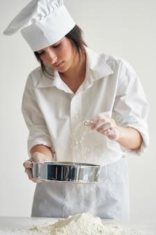 Kobieta kucharz przesiewa mąkę na stole piekarnia gotowanie ciasta