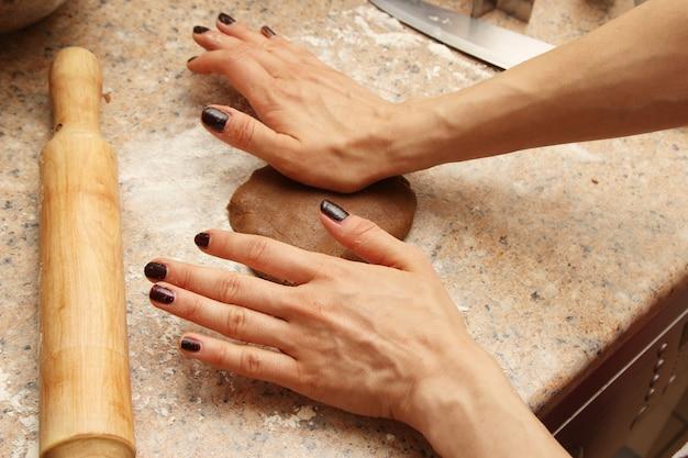 Kobieta kucharz przygotowuje ciasto na ciasteczka w kuchni