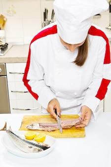 Kobieta kucharz przygotowuje filet z makreli