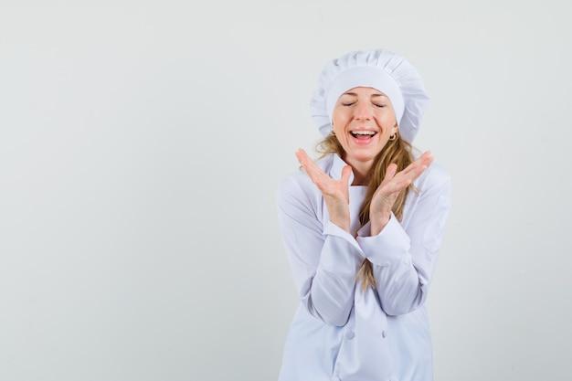 Kobieta kucharz przygotowuje się klaskać w białym mundurze i wygląda na szczęśliwego.